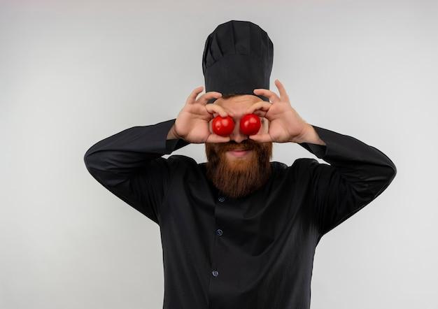 Blij jonge knappe kok in uniform chef-kok tomaten zetten ogen geïsoleerd op witte ruimte