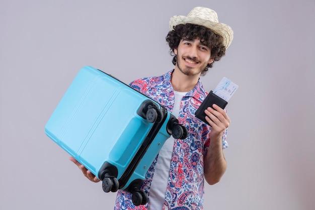 Blij jonge knappe krullende reiziger man met hoed met portemonnee en vliegtuigtickets en koffer op geïsoleerde witte ruimte met kopie ruimte
