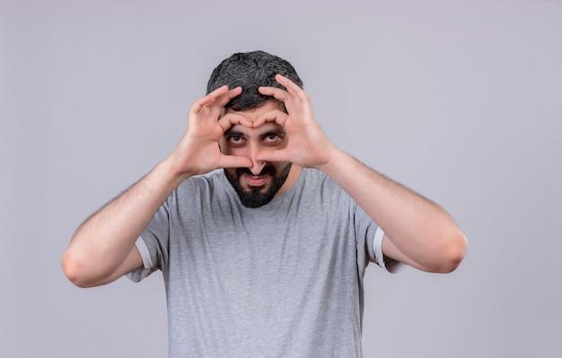 Blij jonge knappe man doet blik gebaar met handen als verrekijker geïsoleerd op een witte muur