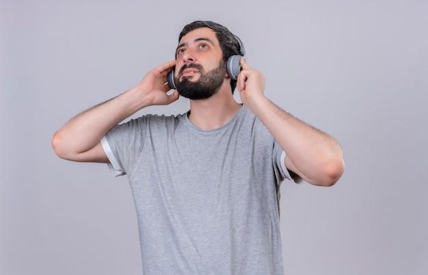 Blij jonge knappe man met koptelefoon luisteren naar muziek en opzoeken met handen op koptelefoon geïsoleerd op een witte muur