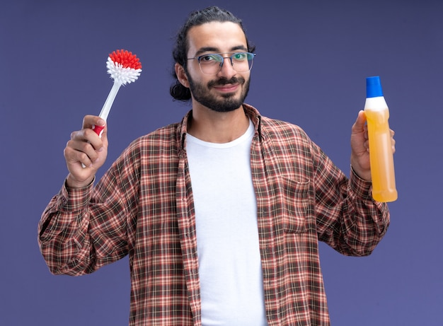 Blij jonge knappe schoonmaakster die de borstel van de t-shirtholding met reinigingsmiddel draagt dat op blauwe muur wordt geïsoleerd