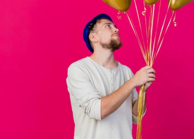 Blij jonge knappe slavische feestjongen die feestmuts draagt en naar ballonnen kijkt die op roze muur met exemplaarruimte worden geïsoleerd