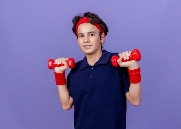 Blij jonge knappe sportieve jongen met hoofdband en polsbandjes met beugels met halters geïsoleerd op paarse muur met kopie ruimte
