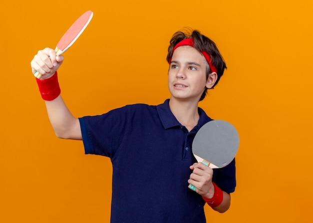 Blij jonge knappe sportieve jongen met hoofdband en polsbandjes met beugels vasthouden en kijken naar pingpongrackets geïsoleerd op oranje muur met kopie ruimte