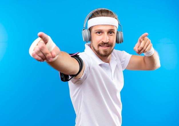 Blij jonge knappe sportieve man met hoofdband en polsbandjes en koptelefoon met telefoon armband wijzend met gewonde pols omwikkeld met verband geïsoleerd op blauwe ruimte