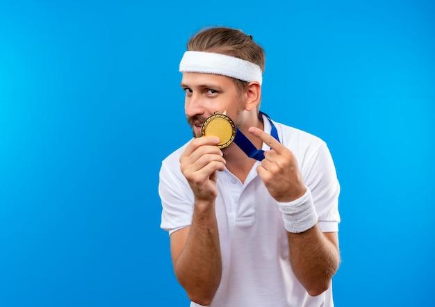 Blij jonge knappe sportieve man met hoofdband en polsbandjes en medaille rond de nek houden en wijzend op medaille geïsoleerd op blauwe ruimte