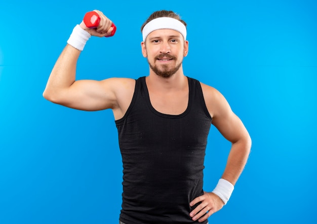Blij jonge knappe sportieve man met hoofdband en polsbandjes halter opheffen en hand op taille zetten geïsoleerd op blauwe ruimte