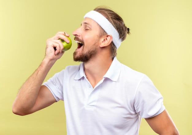 Blij jonge knappe sportieve man met hoofdband en polsbandjes houden en proberen te bijten appel met gesloten ogen geïsoleerd op groene ruimte