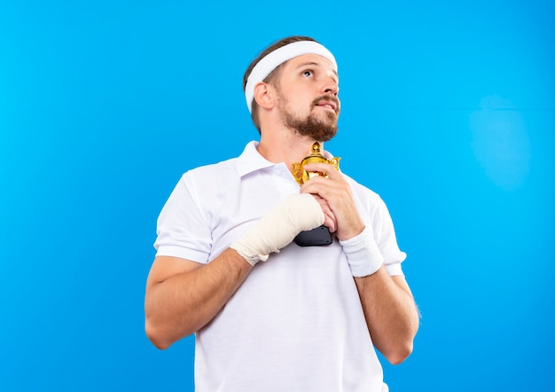Blij jonge knappe sportieve man met hoofdband en polsbandjes houden winnaar beker en opzoeken met gewonde pols omwikkeld met verband geïsoleerd op blauwe ruimte