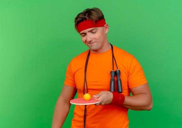 Blij jonge knappe sportieve man met hoofdband en polsbandjes met springtouw om nek vasthouden en kijken naar pingpongracket met bal erop geïsoleerd op groene muur