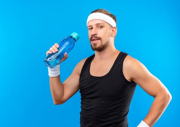 Blij jonge knappe sportieve man met hoofdband en polsbandjes met waterfles op zoek geïsoleerd op blauwe ruimte