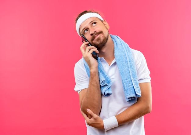 Blij jonge knappe sportieve man met hoofdband en polsbandjes praten over de telefoon opzoeken met handdoek om nek geïsoleerd op roze ruimte