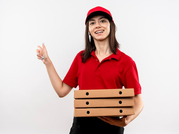 Blij jonge levering meisje dragen rode uniform en pet houden stapel pizzadozen wijzend met wijsvinger naar de zijkanten glimlachend vrolijk staande op witte achtergrond