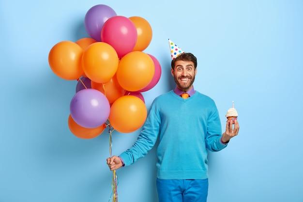 Blij jonge man met haren, houdt heerlijke kleine muffin, bos van gekleurde ballonnen