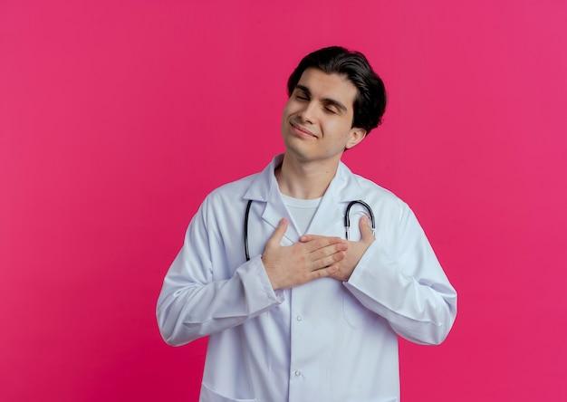 Blij jonge mannelijke arts die medische mantel en stethoscoop draagt die handen op hart met gesloten ogen houdt die op roze muur met exemplaarruimte wordt geïsoleerd
