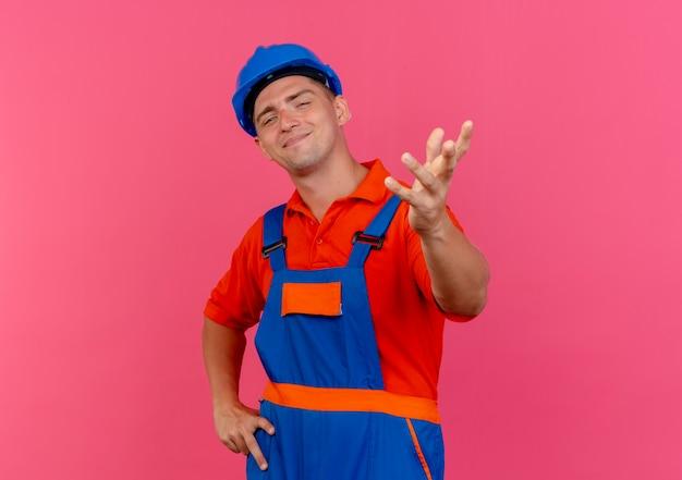 Blij jonge mannelijke bouwer die uniform en veiligheidshelm draagt die hand aan camera stak en andere hand op roze heup zetten
