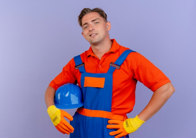 Blij jonge mannelijke bouwer die uniform in handschoenen draagt die veiligheidshelm houdt en handen op heup zet die op paars wordt geïsoleerd