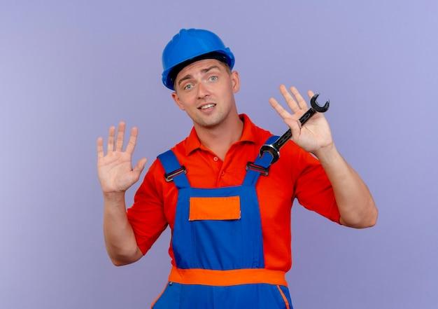 Blij jonge mannelijke bouwer dragen uniform en veiligheidshelm met moersleutel en spreidt handen op paars