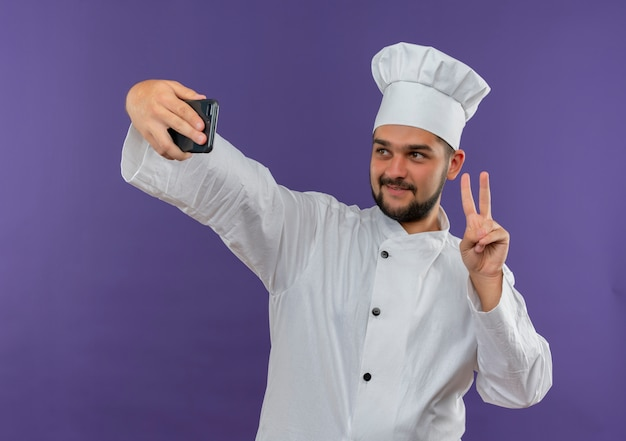 Blij jonge mannelijke kok in chef-kok uniform doet vredesteken en neemt selfie geïsoleerd op paarse ruimte