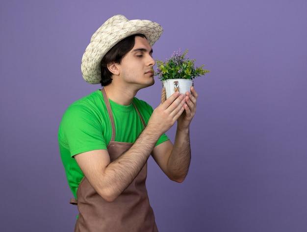 Blij jonge mannelijke tuinman in uniform dragen tuinieren hoed bedrijf en snuiven bloem in bloempot geïsoleerd op paars