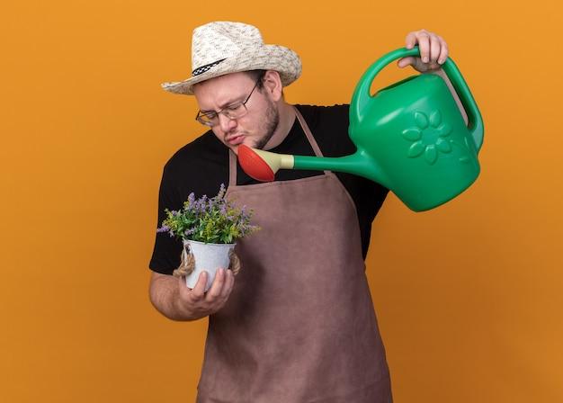 Blij jonge mannelijke tuinman tuinieren hoed en handschoenen dragen bloem in bloempot met gieter geïsoleerd op oranje muur water geven