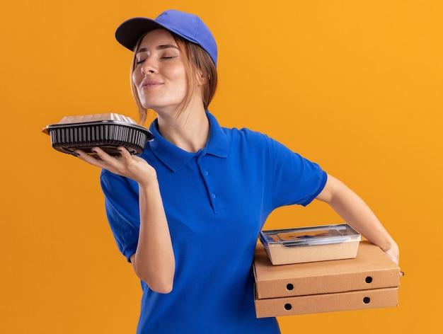 Blij jonge mooie bezorger in uniform houdt en snuift papieren voedselpakketten containers op pizzadozen op oranje