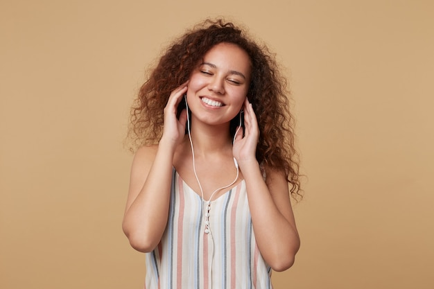 Blij jonge mooie bruinharige krullende vrouw die haar ogen gesloten houdt terwijl ze geniet van muzieknummer in haar koptelefoon en mooi lacht, geïsoleerd op beige