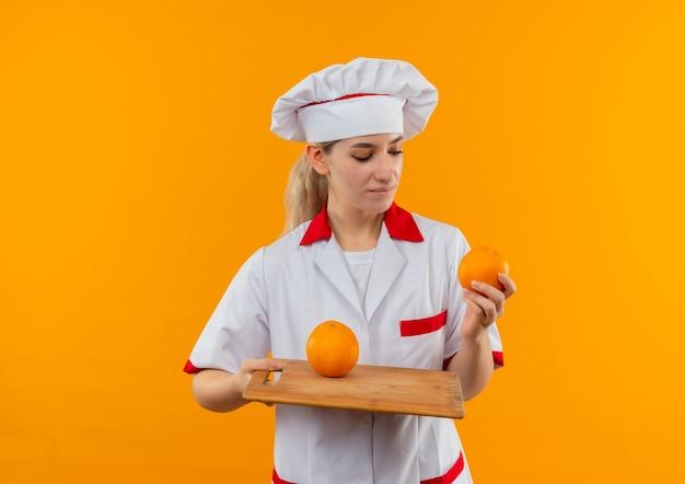 Blij jonge mooie kok in chef-kok uniforme bedrijf oranje en snijplank kijken naar oranje het geïsoleerd op oranje ruimte
