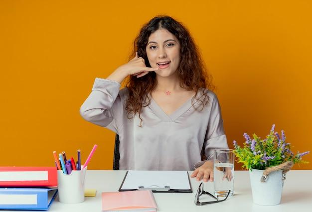 Blij jonge mooie vrouwelijke beambte zittend aan een bureau met office-hulpprogramma's die telefoongesprek gebaar geïsoleerd op oranje tonen