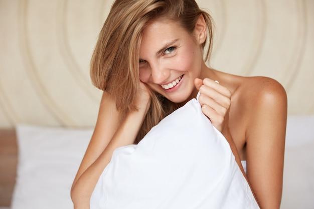 Blij jonge mooie vrouwelijke model met gelukkige uitdrukking en naakte lichaam, vormt op comfortabel bed in modern appartement, glimlacht gelukkig als geweldige ochtend geniet en nieuwe dag begint. bed tijd concept