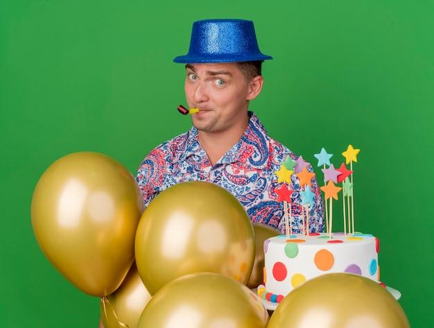 Blij jonge partij kerel die blauwe hoed draagt die zich achter ballons bevindt die cake blazende partijventilator houdt die op groen wordt geïsoleerd