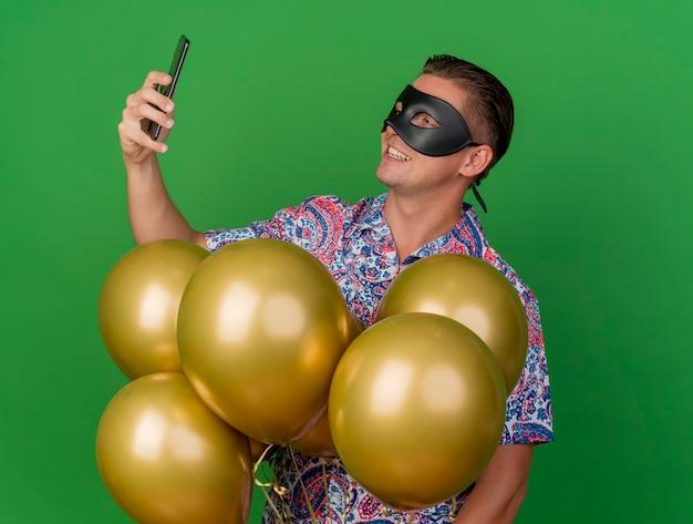 Blij jonge partij kerel dragen maskerade oogmasker staande onder ballonnen houden en kijken naar telefoon geïsoleerd op groen