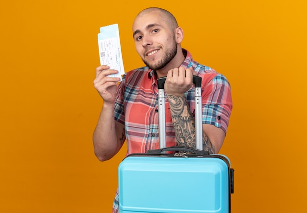 Blij jonge reiziger man met koffer en vliegtickets geïsoleerd op oranje muur met kopie ruimte