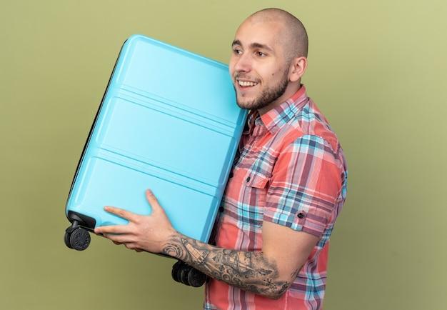 Blij jonge reiziger man staande zijwaarts met koffer geïsoleerd op olijfgroene muur met kopieerruimte