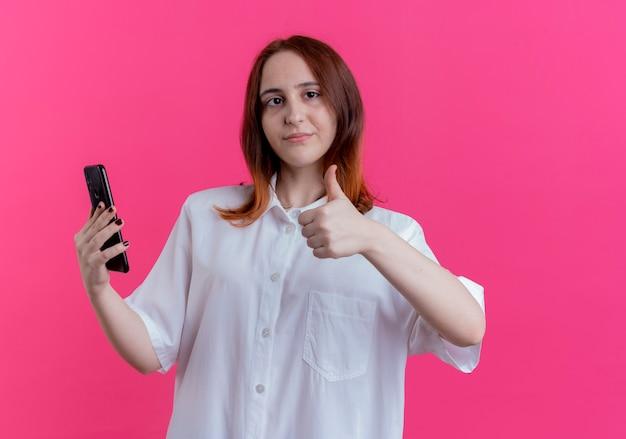 Blij jonge roodharige meisje met telefoon en haar duim omhoog geïsoleerd op roze
