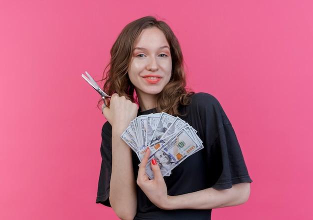 Blij jonge slavische vrouwelijke kapper die eenvormige holdingsschaar en geld draagt die op roze achtergrond met exemplaarruimte wordt geïsoleerd