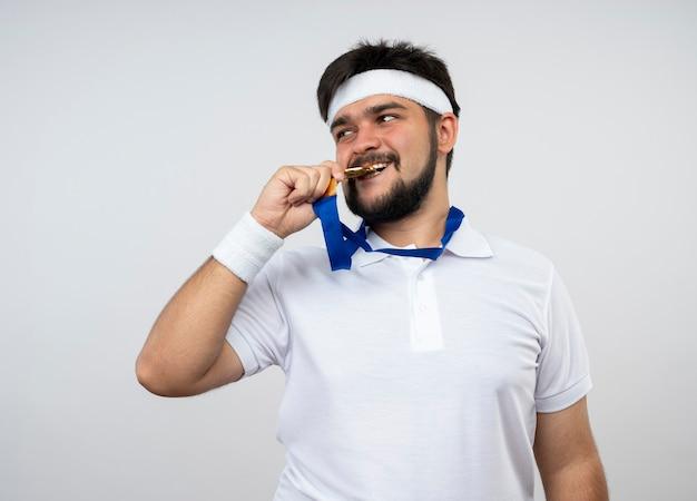 Blij jonge sportieve man kijken naar kant dragen hoofdband en polsband dragen en bijt medaille geïsoleerd op een witte muur