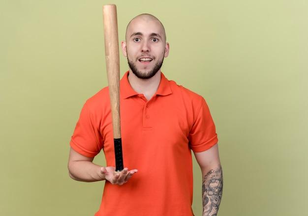 Blij jonge sportieve man met beisbol bit op palm geïsoleerd op olijfgroene muur