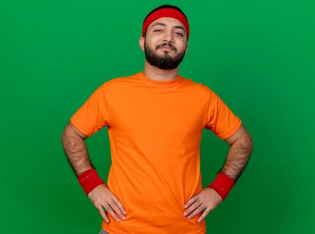 Blij jonge sportieve man met hoofdband en polsband handen op heup geïsoleerd op groene achtergrond