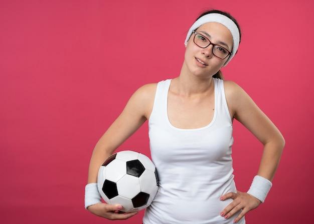 Blij jonge sportieve vrouw in optische bril met hoofdband en polsbandjes legt hand op taille en houdt bal geïsoleerd op roze muur
