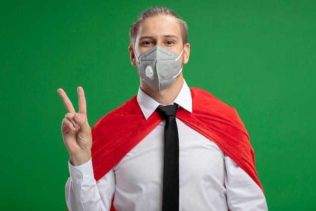 Blij jonge superheld kerel die medische masker en stropdas draagt ?? die vredesgebaar toont dat op groene achtergrond wordt geïsoleerd