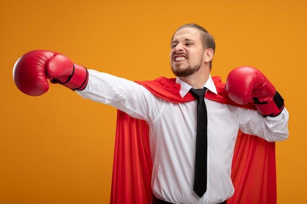 Blij jonge superheld man met stropdas en bokshandschoenen hand aan kant houden geïsoleerd op oranje