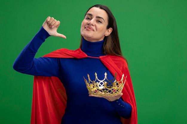Blij jonge superheld meisje bedrijf kroon weergegeven: duim omlaag geïsoleerd op groen