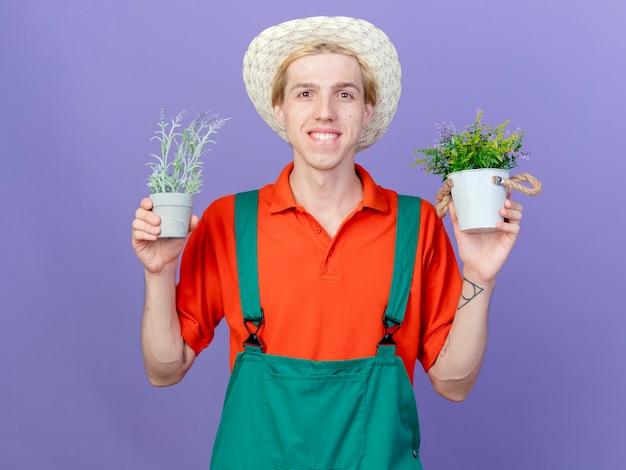 Blij jonge tuinman man met jumpsuit en hoed met potplanten