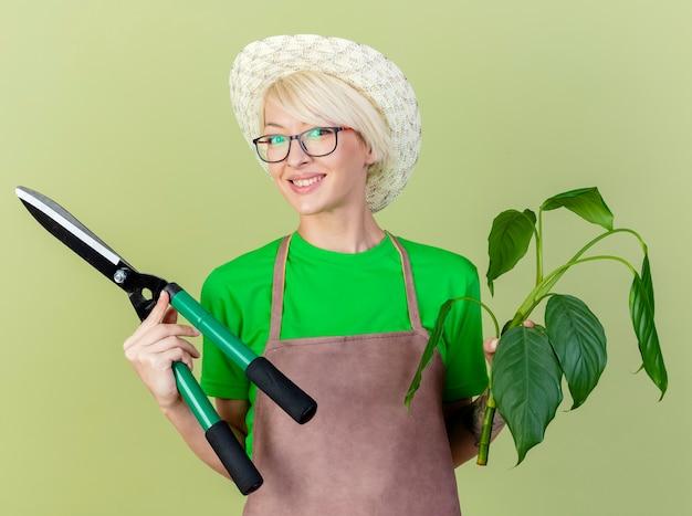 Blij jonge tuinman vrouw met kort haar in schort en hoed met plant en heggenschaar
