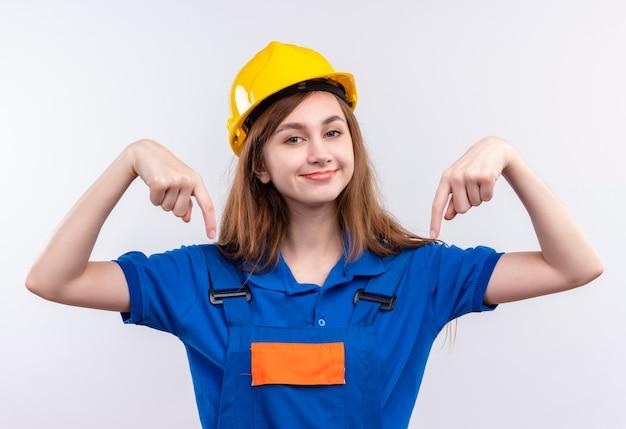 Blij jonge vrouw bouwer werknemer in bouw uniform en veiligheidshelm wijzen met vingers naar zichzelf, trots voelen