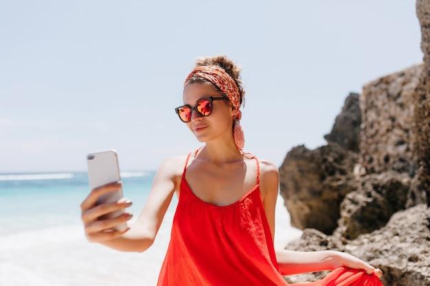 Blij jonge vrouw die met haarlint selfie maakt bij oceaankust. buiten foto van gelukkig wit meisje dat foto van zichzelf op het strand.