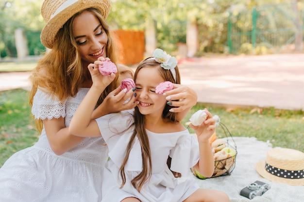 Blij jonge vrouw en opgewonden meisje in witte kledij zittend op een deken met een fruitmand. buitenfoto van elegante dame die tijdens de lunch met dochter voor de gek houdt.