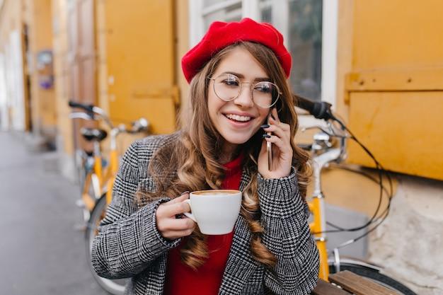 Blij jonge vrouw in grijze jas praten aan de telefoon en koffie drinken in straatcafé