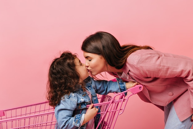 Blij jonge vrouw kussen krullende dochter. schattige jongen zit in winkelwagen.